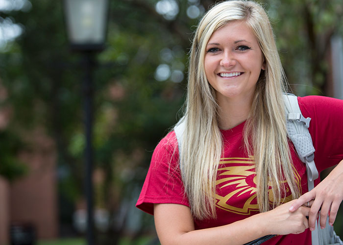 Smiling female student - outside in Coe shirt