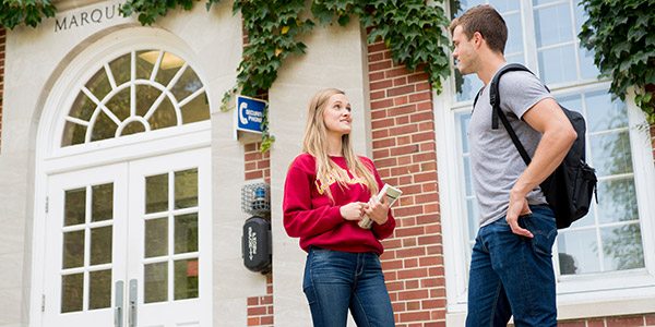 Two students talking in front of Marquis Hall