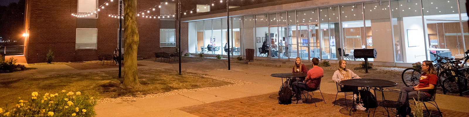 Students conversing outside at night