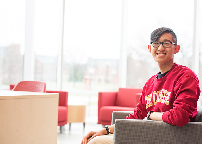 Smiling male student - sitting in chair