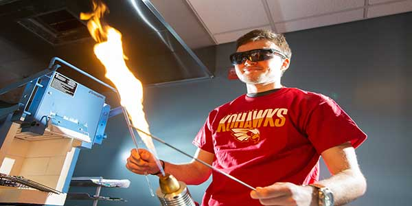 Student in a lab with safety goggles working with fire