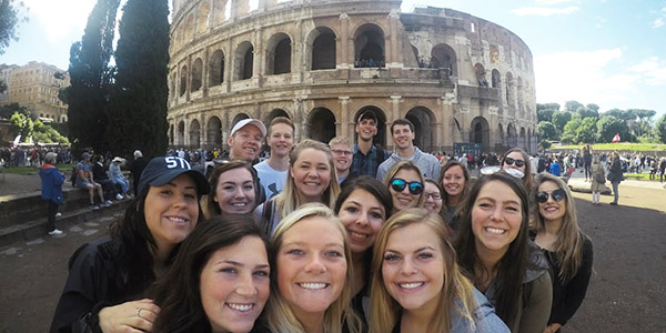 Students take a selfie in front of the Colosseum in Rome.