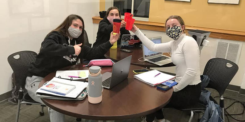 Three students raise their glasses in cheers while studying in the library