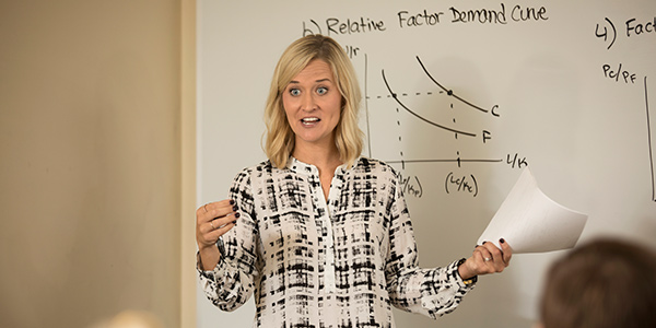 A female professor teaches in front of a white board
