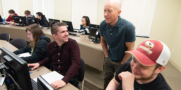 Professor working with students on computers