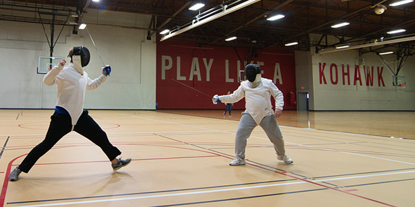 Two Coe students wear fencing gear as they duel in a friendly match