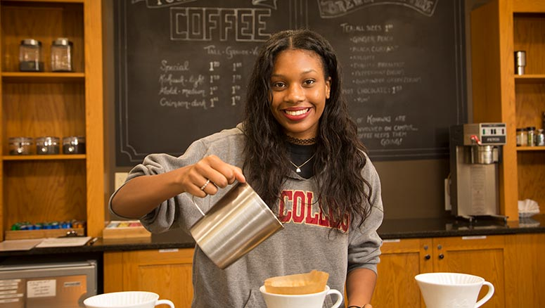 Student pouring coffee at the Coffee Shop