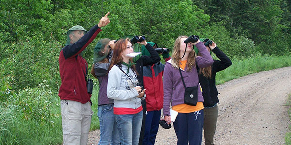 Professor pointing out wildlife to students with binoculars