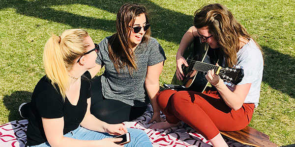Student playing guitar with friends outside