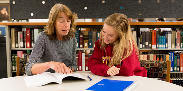 Student and faculty member working through an assignment