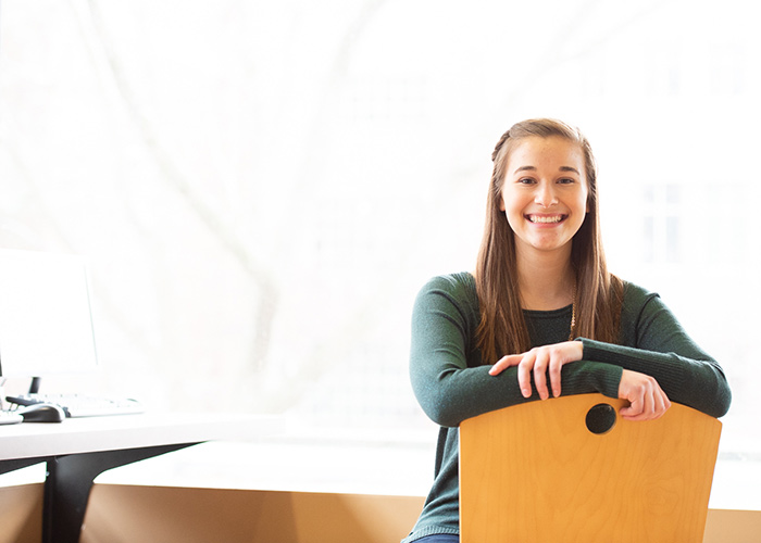 Smiling female student - sitting in chair