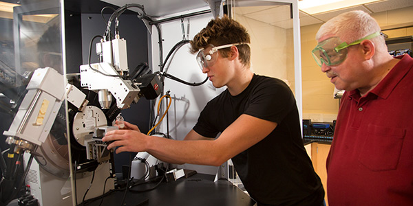 Student and faculty member working with scientific instruments