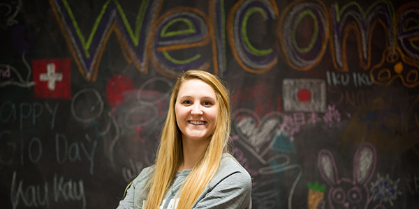 Coe student standing in front of the chalk wall in the intercultural center