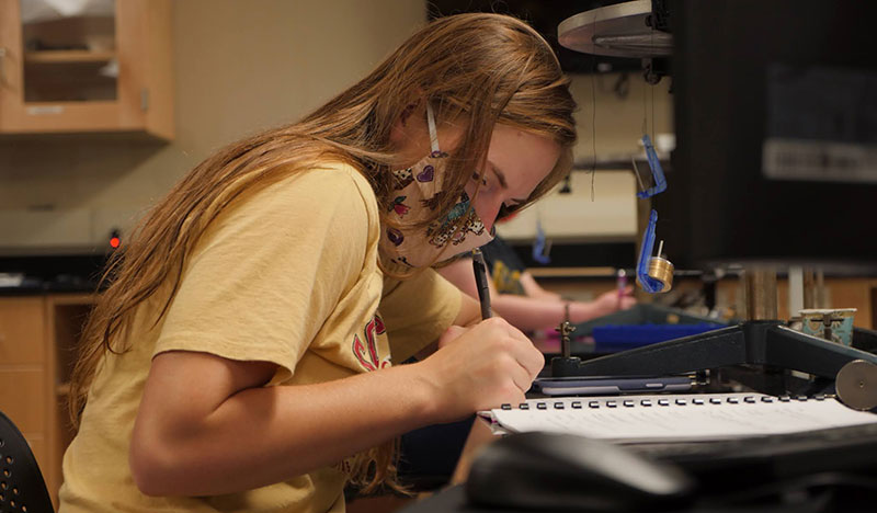 A physics student takes notes near lab equipment