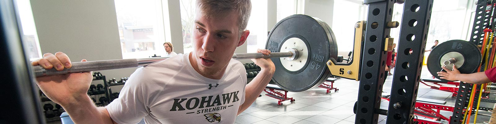 Coe student lifting weights