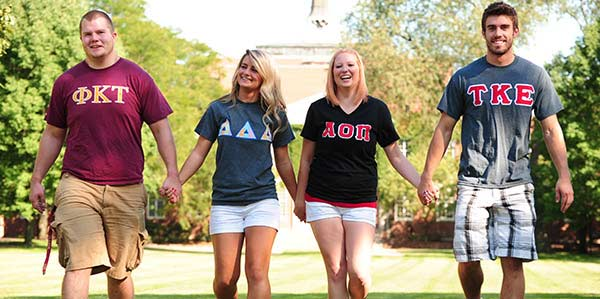 Fraternity men and sorority women wearing their letters and holding hands as they walk across the quad
