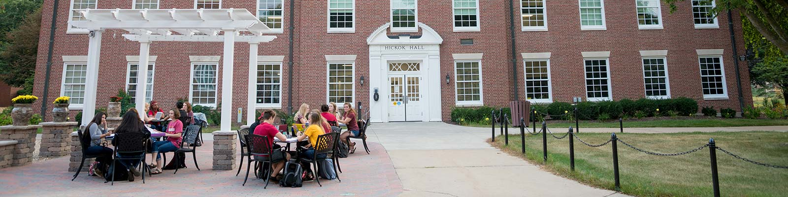 a group of students sitting in the patio area in front of Hickok Hall