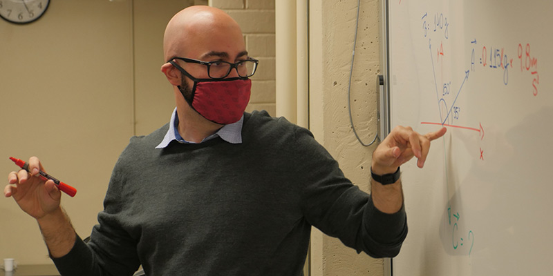 A physics professor gestures to work on a white board
