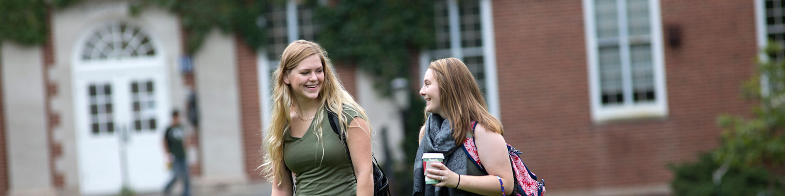 Smiling female students talking while walking